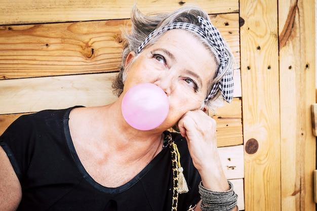 トレンディなメイクと灰色の髪がピンクの風船ガムを吹いて見上げる代替の珍しいかなりシニア白人女性-人生を楽しんでいる古い若者の素敵な肖像画