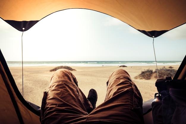 바다 수평선을보고 자유를 즐기는 해변에서 무료 캠핑 텐트 밖에 누워 트레킹 옷을 입은 남자와 대체 휴가 개념