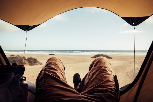Alternative vacation concept with man in trekking clothes laying outside the tent campiing free at the beach looking the ocean horizon and enjoying the freedom - outdoor natural tourism for traveler