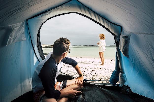 Альтернативный отдых, наслаждаясь полной свободой с палаткой, разбитой на белом песчаном пляже и голубом океане и небе. пара кавказских людей наслаждаются миром в летних каникулах, страстных приключениях, и наслаждаются.