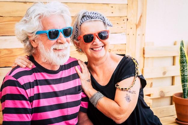 Альтернативная молодая пожилая пожилая пара с белыми волосами, наслаждающаяся вместе обниманием и улыбкой на свежем воздухе - модный и цветной образ для людей без ограничений по возрасту