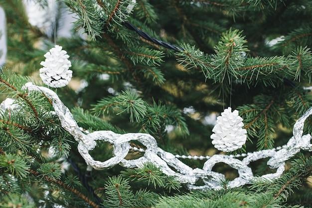 알루미늄 호일 및 야외 크리스마스 트리에 그려진 소나무 콘 수제 장식. 환경, 재활용, 업 사이클링 및 제로 폐기물 개념. 선택적 초점, 복사 공간