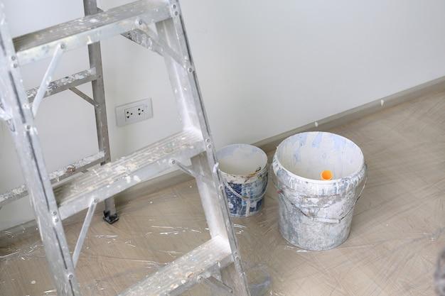새 집의 빈 방에 알루미늄 사다리와 페인트 통.