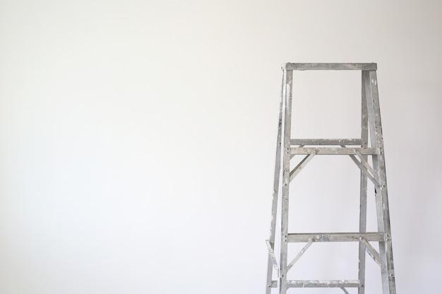 技術者がより高い仕事に使用するための新しい家の空の部屋のアルミニウムはしご。コピースペースのある画像