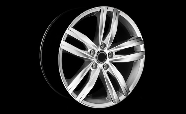 Aluminium modern car wheel rim in dramatic light at night. vehicle rim isolated on black background.
