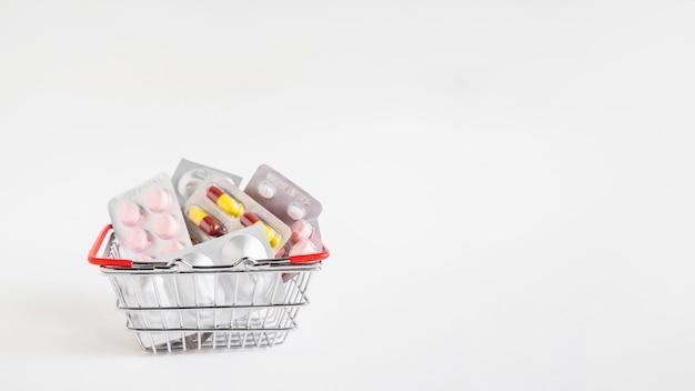 Алюминиевая корзина с множеством блистер на белом фоне