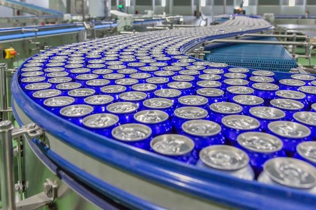 음료 용 알루미늄 음료 캔은 큰 공장에서 컨베이어 벨트로 움직입니다.