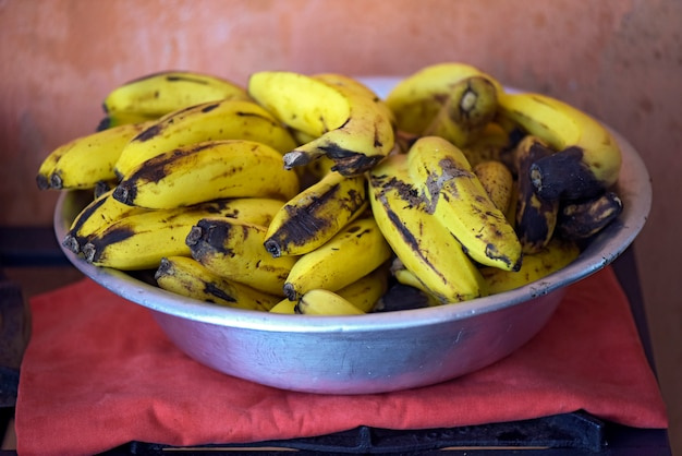 Aluminum bowl with bunch of very ripe bananas