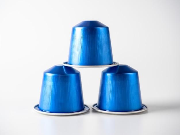 コーヒーマシン用の挽いたコーヒーと青い色のアルミニウムカプセルは、白い背景の上に立っています。孤立したオブジェクト、反射。カプセルのピラミッド。