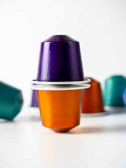 コーヒーマシン用の挽いたコーヒーとオレンジと紫の色のアルミニウムカプセルは、白い背景の上に立っています。カプセルのピラミッド。コーヒーを保存して作る現代の方法