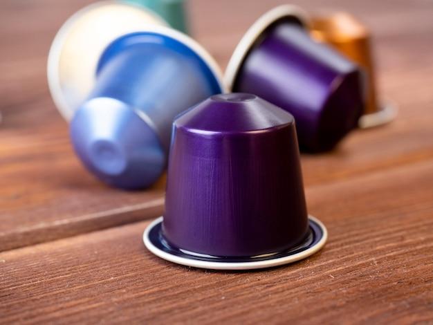 木製の背景に芳香の挽いたコーヒーとアルミニウムカプセル。正面図