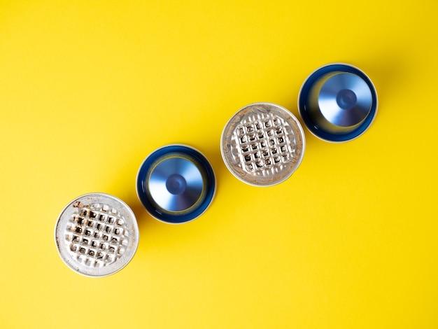 黄色の背景に挽いたコーヒーとアルミニウムカプセル。それらのいくつかが使用されます。製品の保管と再利用のための最新のソリューションの概念。上面図、フラットレイ