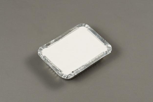 灰色の背景に配達用に準備された温かい食べ物を取るためのアルミニウム容器