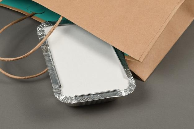 配達用に用意された温かい食べ物を取るためのアルミニウム容器。家にいる