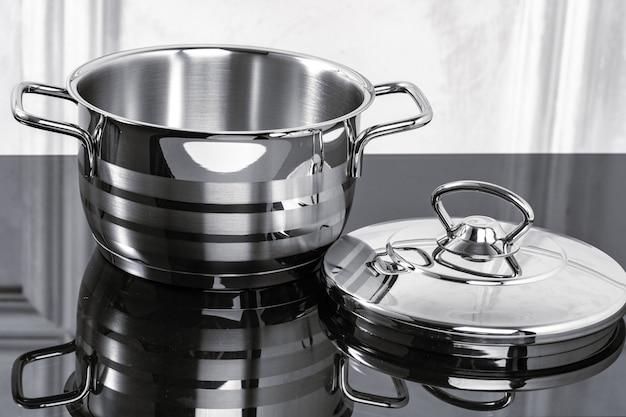 Алюминиевая посуда на черной индукционной плите против серой стены, космос экземпляра