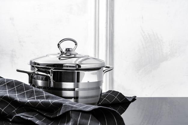 Алюминиевая посуда на черной индукционной плите на серой стене