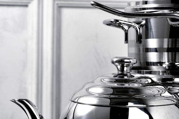 Алюминиевая посуда на черной индукционной плите против серой стены