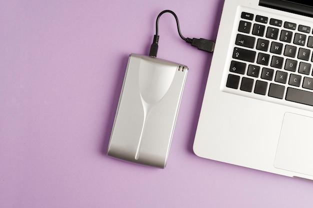 アルミニウム外付けハードドライブ部分ラップトップビュー紫色の背景上面図