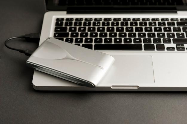 Алюминиевый внешний жесткий диск с usb-кабелем, подключенным к ноутбуку на черном офисном столе
