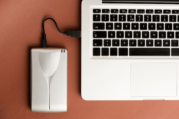 Алюминиевый внешний жесткий диск с usb-кабелем, подключенным к ноутбуку на коричневом офисном столе
