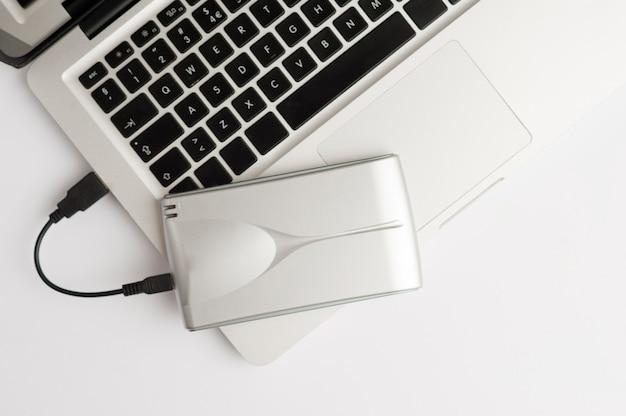 Алюминиевый внешний жесткий диск с кабелем usb на верхней части ноутбука на белом офисном столе. вид сверху