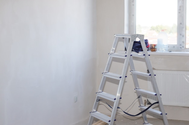 Алюминиевая складная лестница в комнате с белой штукатуркой стены и окна. ремонт жилья в новом доме. скопируйте пространство.