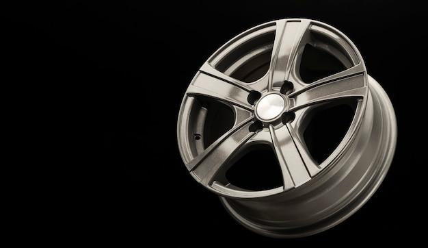 Aluminum gray alloy wheel on black background, copyspace.