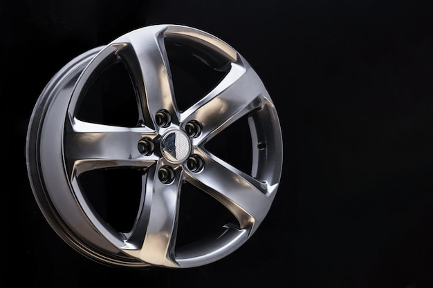 Aluminum metal wheel rim texture, beautiful chrome gray asphalt color alloy car wheel on black background, blank space for text