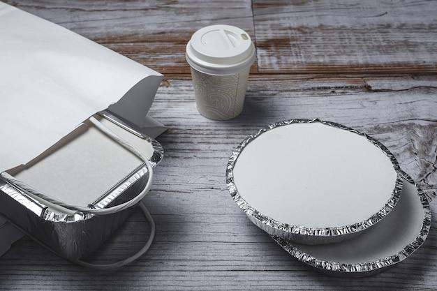 Алюминиевые пищевые контейнеры на вынос, подготовленные к отправке в перерабатываемых бумажных пакетах