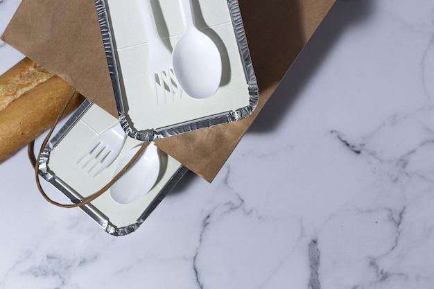 Алюминиевые пищевые контейнеры на вынос, подготовленные к отправке в перерабатываемых бумажных пакетах.