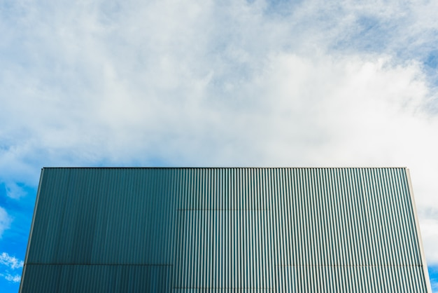 Aluminum wall at the back of a smooth windowless building and blue sky