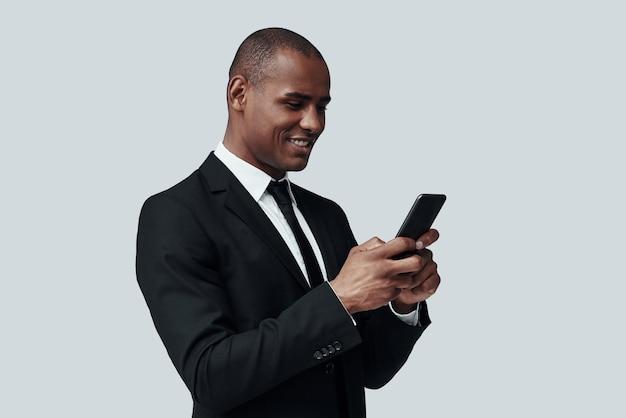 항상 사용할 수 있습니다. 스마트 폰을 사용하고 회색 배경에 서서 웃고 있는 정장 차림의 매력적인 젊은 아프리카 남자