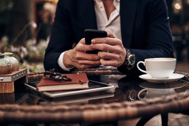 いつでもご利用いただけます。屋外のレストランに座っている間彼のスマートフォンを使用してスマートカジュアルウェアで若い男のクローズアップ