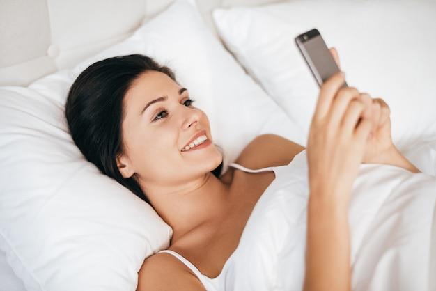 Всегда в наличии для него. красивая молодая женщина улыбается и держит смартфон