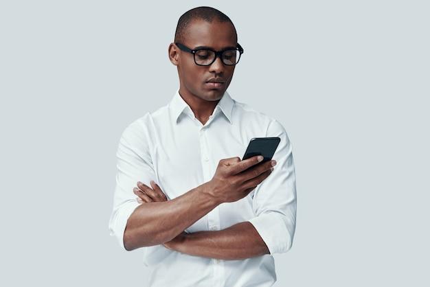 Всегда доступен. красивый молодой африканский человек с помощью смартфона, стоя на сером фоне