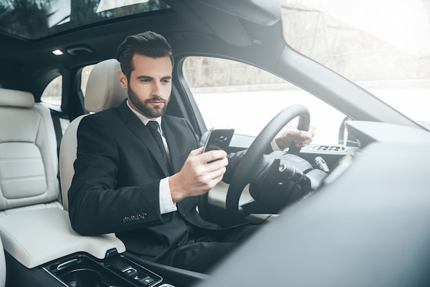 Всегда доступен. красивый молодой бизнесмен, глядя на свой смартфон, сидя на переднем сиденье