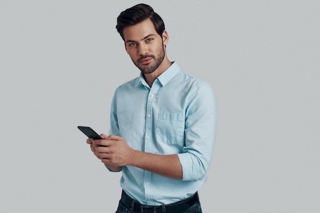いつでもご利用いただけます。灰色の背景に立ってスマートフォンを使用してカメラを見ているハンサムな若い男