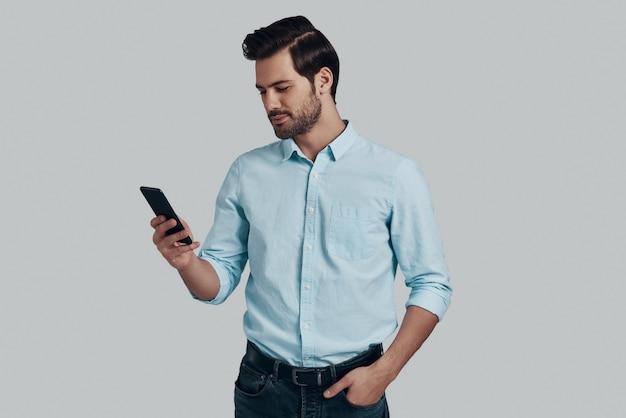 いつでもご利用いただけます。スマートフォンを使用して、灰色の背景に立って笑っているハンサムな若い男