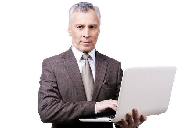 Всегда занят. красивый зрелый мужчина в формальной одежде регулирует держа ноутбук, стоя на белом фоне