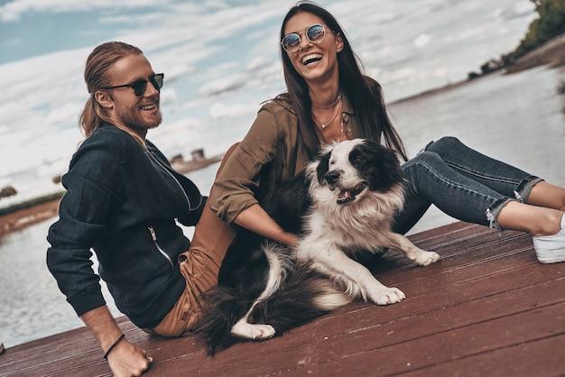 Всегда носятся друг с другом. красивая молодая пара играет с собакой, сидя на берегу озера на открытом воздухе
