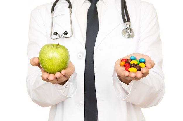 Always a choice there. cropped shot of a doctor holding a green apple and pills in his hands