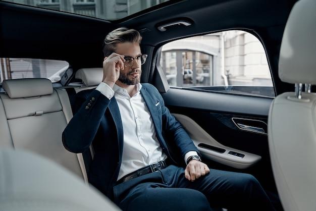 항상 자신감이 있습니다. 차에 앉아있는 동안 그의 안경을 조정 전체 정장에 잘 생긴 젊은 남자