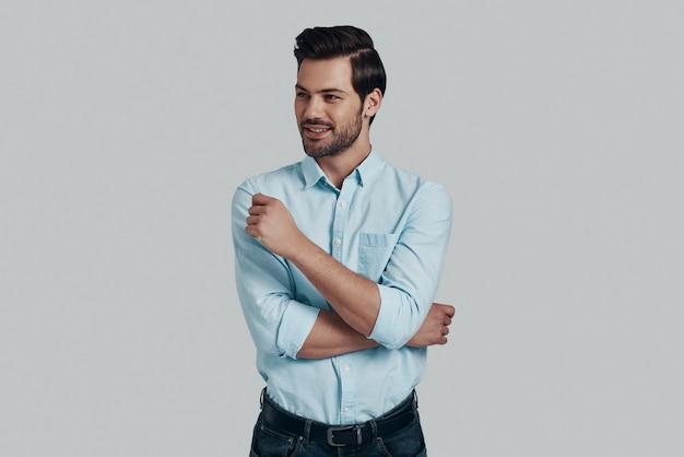 常に自信を持っています。灰色の背景に立っている間、目をそらして笑っているハンサムな若い男