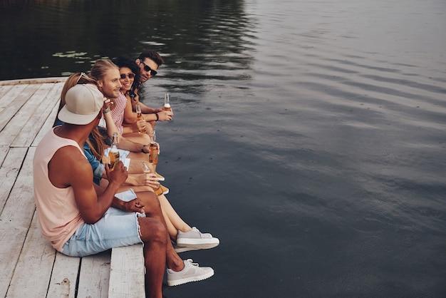 いつも一緒に楽しんでいます。桟橋に座って笑顔でビールを飲みながらカジュアルな服装で幸せな若者のグループ