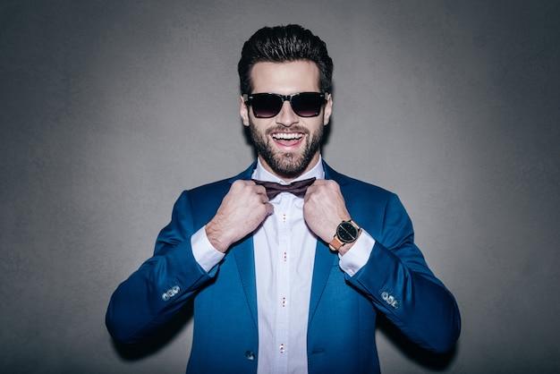 いつもいい気分!彼の蝶ネクタイを調整し、灰色の背景に立っている間笑顔でカメラを見ているサングラスをかけているハンサムな若い陽気な男のクローズアップ