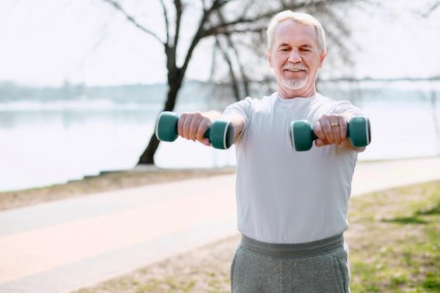 Всегда в форме. энергичный зрелый мужчина поднимает гантели и смотрит вниз