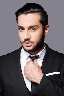 常にスタイリッシュ。灰色の背景に立っている間彼のネクタイを調整する正装のハンサムな若い男