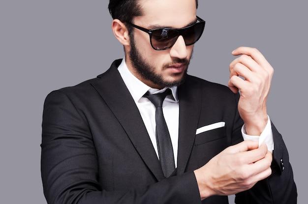 常にスタイリッシュ。灰色の背景に立っている間彼の袖を調整する正装のハンサムな若い男