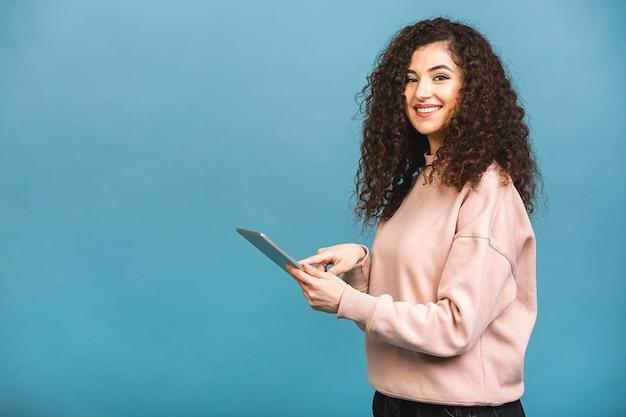 常に連絡を取り合う!青い背景で隔離のタブレットを使用して笑っている美しい巻き毛の少女。テキスト用のスペースをコピーします。