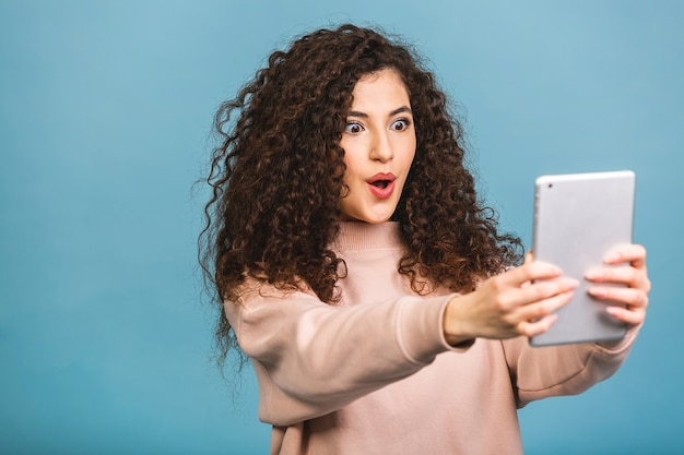 常に連絡を取り合う!青い背景で隔離のタブレットを使用して笑っている美しい巻き毛の少女。